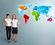 Giovani donne che presentano la mappa di mondo variopinta Fotografia Stock Libera da Diritti