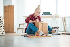 Giovani donne che riparano mobilia a casa immagine stock libera da diritti