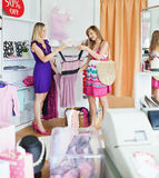 Giovani donne che scelgono insieme i vestiti Immagini Stock Libere da Diritti