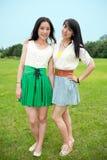 Giovani donne che si levano in piedi sul sorridere dell'erba Immagini Stock