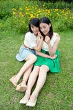 Giovani donne che si siedono levarsi in piedi sorridente sull'erba Fotografie Stock