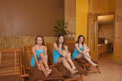 Giovani donne che si siedono sui loungers davanti a sauna fotografie stock