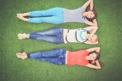 Giovani donne che si trovano sull'erba verde Giovani donne Fotografie Stock