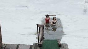 Giovani donne che spruzzano in un foro del ghiaccio video d archivio