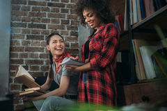 Giovani donne che studiano insieme ai libri ed a sorridere Immagini Stock Libere da Diritti