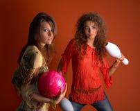 Giovani donne che tengono la sfera di bowling immagine stock