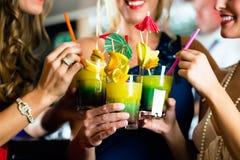 Giovani donne con i cocktail in club o in Antivari Fotografie Stock