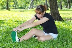 Giovani donne con l'allungamento delle sue gambe Fotografia Stock Libera da Diritti