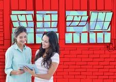 2 giovani donne con la compressa che guarda il nuovo ufficio allinea Parete rossa dei mattoni con le finestre Fotografia Stock