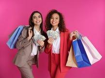 Giovani donne con soldi ed i sacchetti della spesa su fondo immagine stock