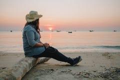 Giovani donne del fondo di viaggio le belle si siedono la spiaggia sola con il mare Immagini Stock