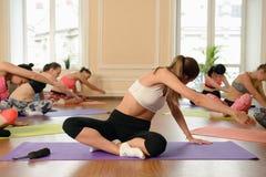 Giovani donne del gruppo che allungano e yoga di pratiche Fotografia Stock Libera da Diritti