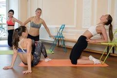 Giovani donne del gruppo che allungano e yoga di pratiche Immagini Stock