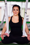 Giovani donne del ritratto che fanno yoga antigravità nella posizione di loto Forma fisica aerea aerea della mosca amache bianche Immagine Stock