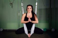 Giovani donne del ritratto che fanno yoga antigravità nella posizione di loto Forma fisica aerea aerea della mosca amache bianche Immagini Stock