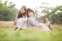 Giovani donne del ritratto due sulla natura delle ukulele Immagine Stock Libera da Diritti