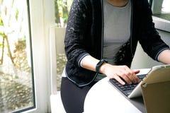 Giovani donne dello studente che indossano banda astuta facendo uso del computer della compressa Immagini Stock