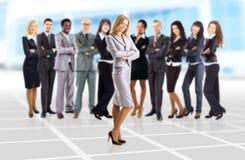 donna di affari ed il suo gruppo sopra il fondo dell'ufficio Immagini Stock Libere da Diritti