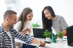 Giovani donne di affari sorridenti che per mezzo del computer portatile alla riunione Fotografia Stock