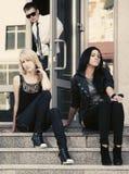 Giovani donne di modo che si siedono sui punti Fotografie Stock