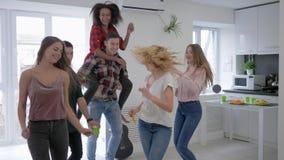 Giovani donne ed uomini felici divertendosi e ballando con le tazze di plastica in loro mani in appartamento privato sul partito