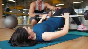 Giovani donne esili che fanno esercizio per le natiche - l'aumento di un corpo che si trova sopra la barra stock footage