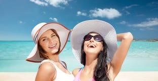 Giovani donne felici in cappelli sulla spiaggia di estate immagine stock libera da diritti