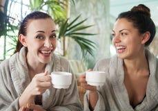Giovani donne felici che bevono tè alla località di soggiorno di stazione termale Fotografia Stock