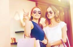 Giovani donne felici con i sacchetti della spesa in centro commerciale immagine stock libera da diritti