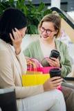 Giovani donne felici con i sacchetti della spesa e le tazze di carta del caffè che si siedono, riposanti e parlanti dopo la compe immagini stock