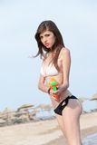 Giovani donne graziose che giocano con la pistola a acqua alla spiaggia Fotografia Stock