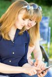 Giovani donne graziose che utilizzano smartphone nel parco di estate Fotografia Stock