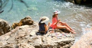 Giovani donne graziose in costume da bagno ed in copertura che si siedono sulle rocce vicino al mare video d archivio