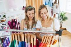 Giovani donne intelligenti che scelgono le camice variopinte Fotografia Stock