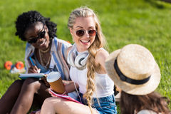 Giovani donne multietniche che parlano mentre studiando sull'erba verde in parco Immagini Stock Libere da Diritti