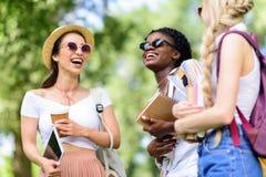 Giovani donne multietniche che tengono i libri e compressa digitale mentre parlando nel parco Immagini Stock Libere da Diritti