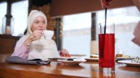 Giovani donne musulmane che si siedono e che parlano in caffè moderno Una donna mescola una bevanda luminosa con una paglia video d archivio