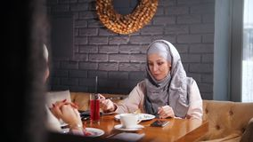 Giovani donne musulmane che si siedono, mangianti e parlanti in caffè moderno video d archivio