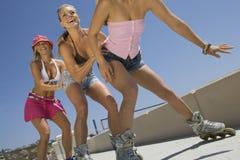 Giovani donne sopra nella linea pattini Immagine Stock