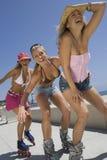 Giovani donne sopra nella linea pattini Immagini Stock