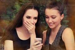 Giovani donne sorprese dal messaggio di testo Fotografia Stock Libera da Diritti