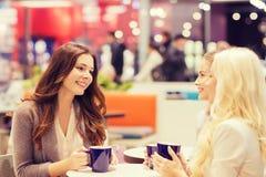 Giovani donne sorridenti che bevono caffè in centro commerciale Immagine Stock