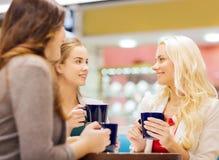 Giovani donne sorridenti con le tazze in centro commerciale o caffè Fotografia Stock