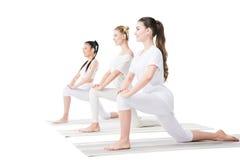 Giovani donne sorridenti nell'yoga di pratica degli abiti sportivi sulle stuoie Immagine Stock Libera da Diritti
