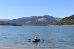 Giovani donne sulla barca con le pagaie sul lago Bicaz romania Lungo le montagne verdi fotografia stock