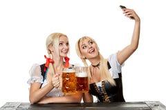 Giovani donne in vestiti bavaresi tradizionali, dirndl o tracht, su fondo bianco fotografia stock libera da diritti