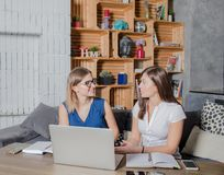 Giovani due colleghi che hanno conversazione, download aspettante dell'archivio sul NET-libro portatile Fotografia Stock Libera da Diritti