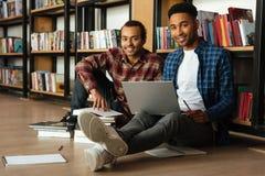 Giovani due libri di lettura africani degli studenti degli uomini facendo uso del computer portatile Immagini Stock Libere da Diritti