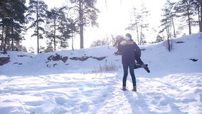 Giovani e belle coppie nell'amore che cammina nel legno di inverno stock footage