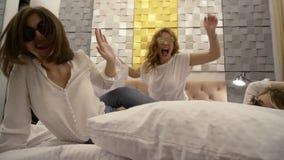 Giovani e belle ragazze in abbigliamento casual che salta sul letto in occhiali da sole Celebrazione dell'addio al nubilato del ` stock footage